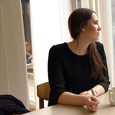 Opiskelija katselee yliopiston kahvilan ikkunasta ulos.