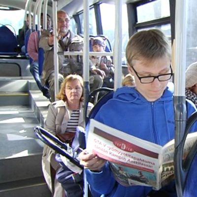 Ihmisiä HSL:n bussissa.