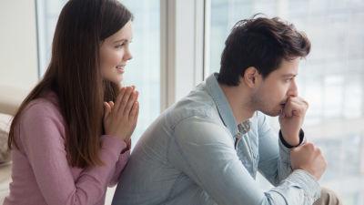 Ung kvinna sitter bakom ung man och ler, han ser sorgsen och fundersam ut