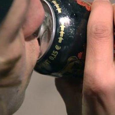 Nuori mies juo alkoholia.
