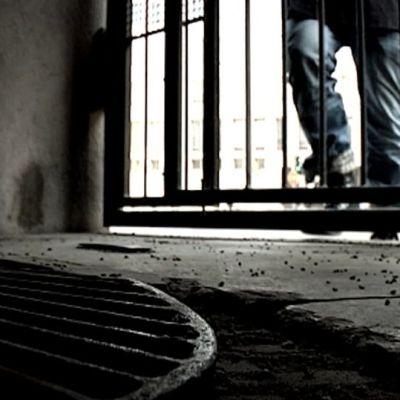 Anonyymi mies kävelee pimeään porttikäytävään.