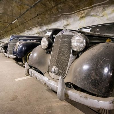 Vanhoja autoja rivissä parkkihallissa.
