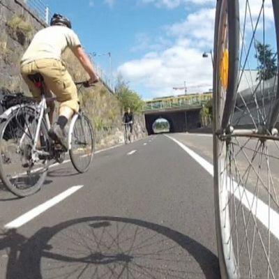 Polkupyöräilijät ajavat pyörätiellä.