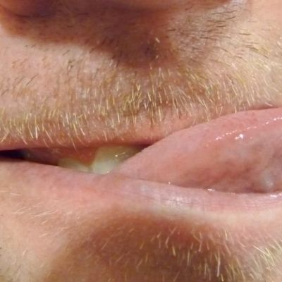Parrakkaan miehen suu, jossa kieli ulkona