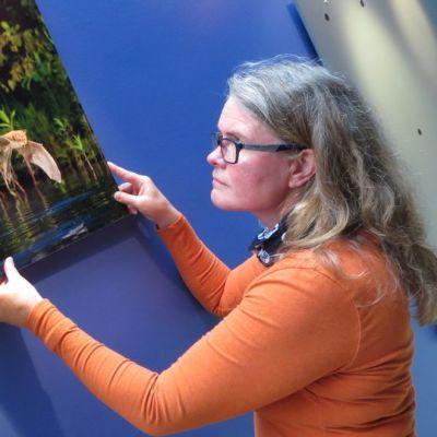 Luontoyrittäjä Elina Enho sovittelee Hannu Männyn lepakkokuvaa valkoselkätikan näköispatsaan viereen.