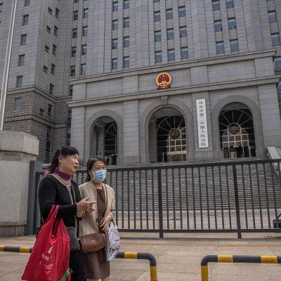 Ihmiset kävelevät oikeustalon ohi, jossa Yang Hengjunin oikeuskäsittely käydään.