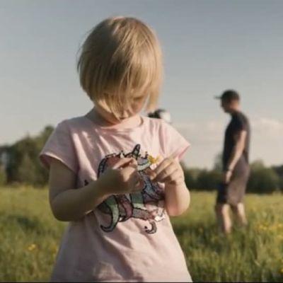 Lapsi seisoo pellolla kuvan etualalla. Aikuiset seisovat taka-alalla.en ollessa takana.