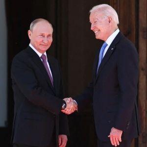 Vladimir Putin och Joe Biden skakar hand framför en stor dörr med amerikanska, ryska och schweiziska flaggor omkring sig.