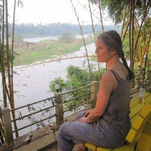Janna Thorström sitter på en bänk och tittar ut över en flod i Indien.