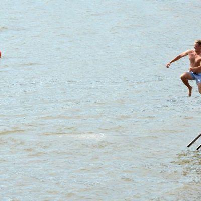 Mies hyppää laiturilta mereen