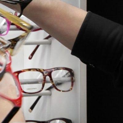 Optikko asettelee silmälaseja näytille.