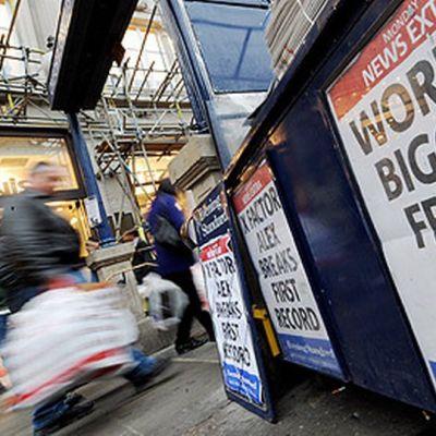 Jalankulkijat kulkevat huijauksesta kertovien uutisotsikoiden ohitse Lontoossa 15. marraskuuta.