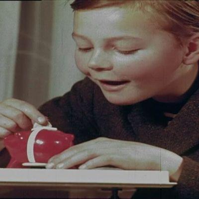 Poika laittaa rahaa säästöpossuun. Kuva 60-luvulta.