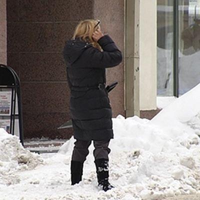 Nainen seisoo auton edessä lapio kädessään.