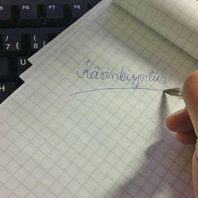 Näppäimistöllä lehtiö, johon on kirjoitettu käsinkirjoitus.