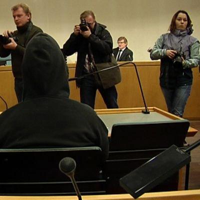 Kuvaajat ottavat valokuvia kirjastopuukotuksesta syytetystä.