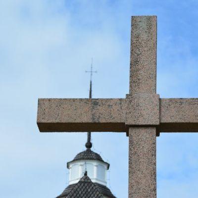 Kirkon torni ja etualalla jyhkeä risti.