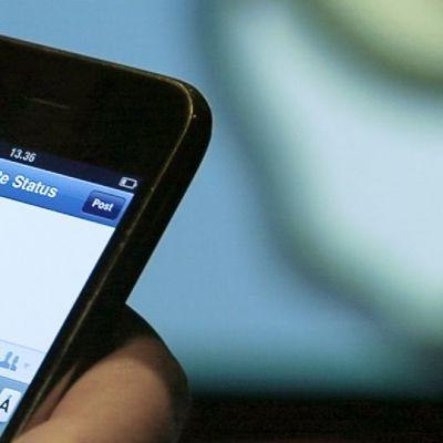 Henkilö käyttämässä Facebookia kännykällä.