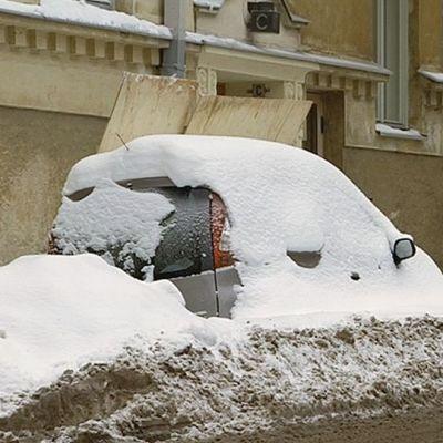 Auto kadun varressa lumikinoksessa.