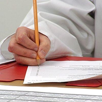 Lääkäri kirjoittaaa paperille.