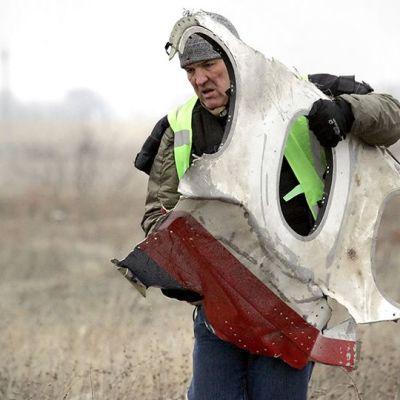 Työntekijä kantaai tuhotun malesialaiskoneen palaa Grabovon kylässä Ukrainassa