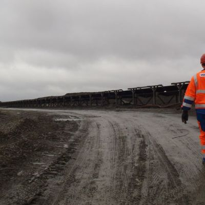 Talvivaaran työntekijä kävelee kuraisella kaivosalueella.