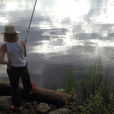 Poika onkii järven rannalla.