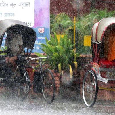 Riksakuskit suojautuvat vesisateelta Intian Amritsarissa.
