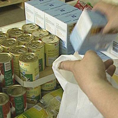 Seurakunnan työntekijä pakkaa ruoka-apukassia.