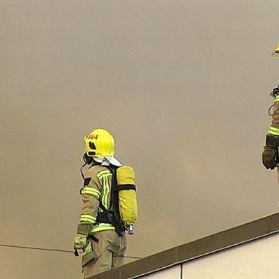Palomiehiä palavan rakennuksen katolla.