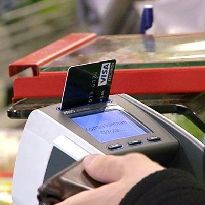 Henkilö maksamssa pankkikortilla kaupan kassalla.