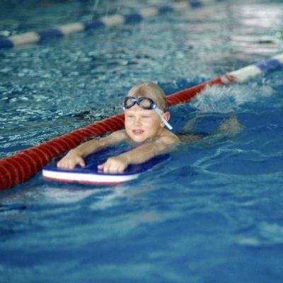 Kaksi lasta harjoittelee uintiliikkeitä uintilaudan avulla.
