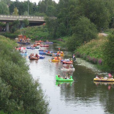 Ihmisiä joessa kuviveneillä Kaljakellunta-tapahtumassa