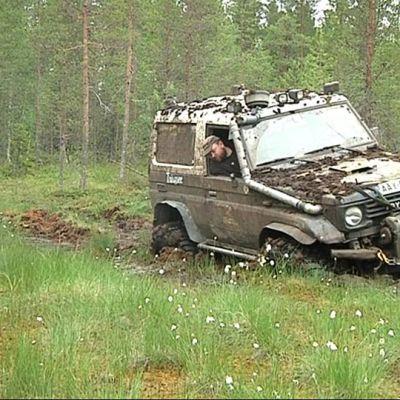 Ossi Kaunisvaara ajaa ja apukuskina toimiva Marko Parttimaa kurkkii kuinka syvälle suohon auto vajoaa.