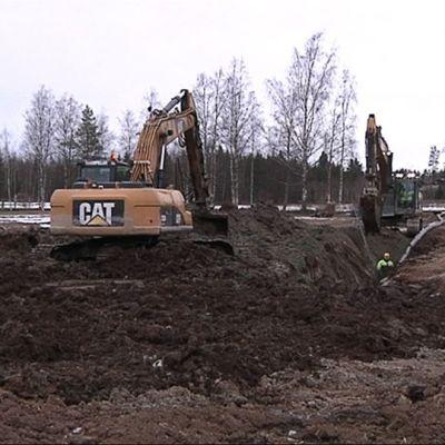 Kälviällä kaksi kaivinkonetta peittää viemärijohtokaivantoa ja työntekijä varmistaa tilanteen kaivannon pohjalla.