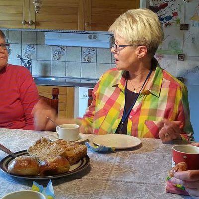 Kolme naista kahvipöydän ääressä.