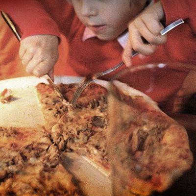 Lapsi syö pizzaa