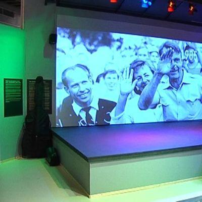 Pori Jazz-aiheinen näyttely. Valkokankaalle heijastettu kuva presidentti Koivistosta jazzeilla.