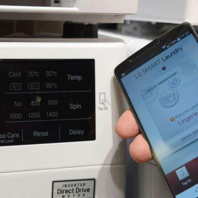 Kuvassa älypesukoneen näyttö ja koneeseen yhteydessä oleva kännykkä