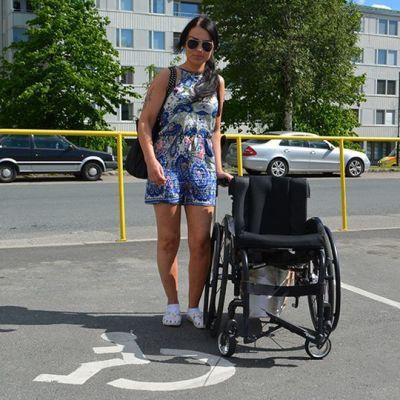 Sanna Palm seisoo pyörätuolin vieressä invapysäköintipaikalla.