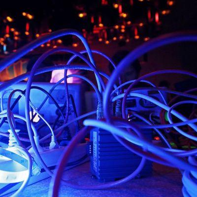 Tietokoneiden johtoja sinisessä valaistuksessa.