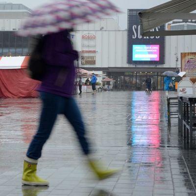 Ihminen kävelee sateenvarjon kanssa, taustalla Kuopion tori