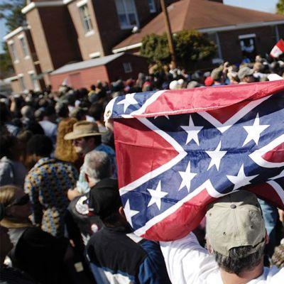 Mies pitelee etelävaltioiden lippua ilmassa.