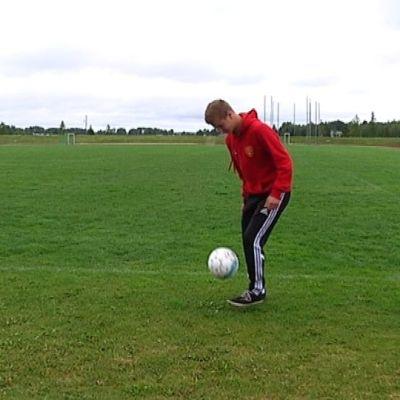 Juniorijalkapalloilja Tuure Mäntynen pompottelee palloa.