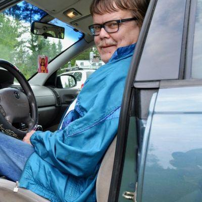 Mies istuu autossa.