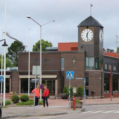 Iitin kunnantalon kellotorni, etualalla seisoo kaksi miestä