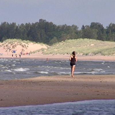 Yyterin hiekkarantaa. Uimareita ja nainen hölkkäämässä uimarantaa.