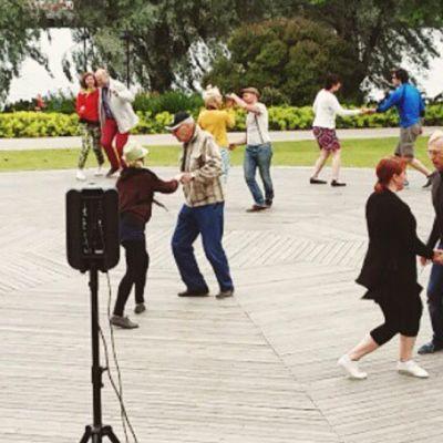 Ihmiset tanssivat Töölönlahden rannalla.