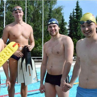 Neljä hengenpelastuskilpailujen mieskilpailijaa altaan reunalla