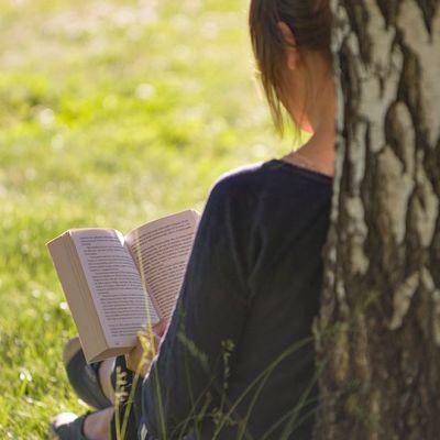 Nainen lukee kesällä ulkona kirjaa koivuun nojaten.